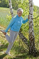 Older female person stretching her leg