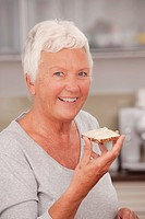 Elderly lady eating a slice of bread and butter