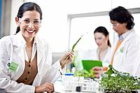 Female scientist holding plants in laboratory