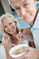 Close_up of a senior man eating spaghetti with a senior woman smiling in the background