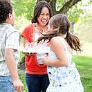 Mother serving birthday cake to children 10_12 in garden