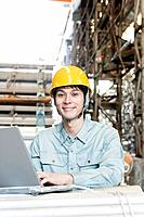 Young Warehouseworker Using Laptop