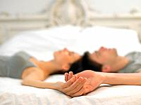 Young couple lying on bed holding hands