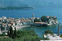 View over the town and bay of Budva. Small beach. Church. Tables on a terrace in the foreground.