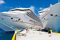 Cruise ship passengers on pier disembarking from Carnival cruise ships Triumph and Ecstasy in Cozumel, Mexico in the Caribbean Sea