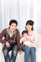 Mother, father and baby boy sitting on couch