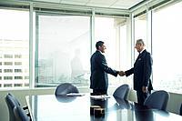 Hispanic businessmen shaking hands in conference room