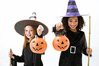 Girls in witch costumes holding jack o´lantern