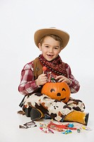 Caucasian boy in cowboy costume eating Halloween candy