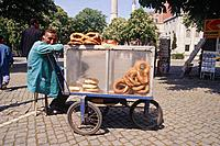 Man on stool selling bread from stall in Aya Sofya Square. Postcards and newspapers behind. Trees.