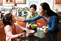Asian mother and daughters eating breakfast in kitchen