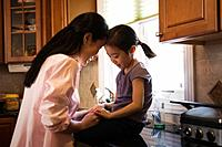 Asian mother comforting daughter in kitchen