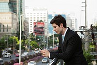 Caucasian businessman text messaging on cell phone outdoors