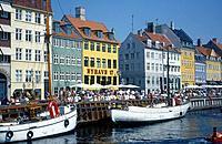 Nyhavn. People sitting on harbour wall. Boats. Buildings. Restaurants / cafes.