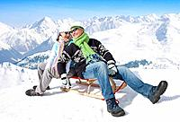 Smiling couple sitting back to back on sled on snowy mountain
