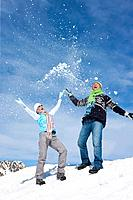 Playful couple throwing snow in sky on mountain