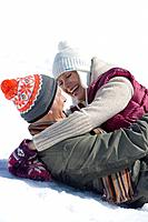 Smiling couple hugging face to face and laying in snow