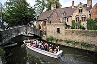 Bonifacius bridge over canal and tourists during sightseeing boat trip in Bruges, Belgium