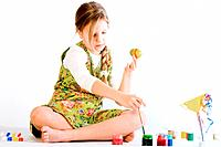 Young girl playing with paint and eggs