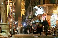 Muslim souk. Narrow streets of city. Night. Cars,people. Minaret lit up.