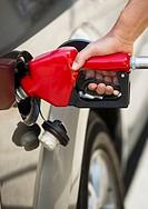 Hand holding fuel pump refueling car