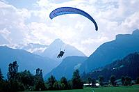 Village in mountains. Person paragliding. Mountains,mist.