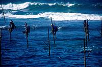 Coast. Sea. Big waves. Fishermen on stilts,perches over water. Rods and lines. Seafishing.