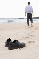 Businessman walking barefoot on beach