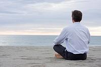 Geschäftsmann meditiert am Strand