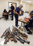 Detroit, Michigan - Police officers examine weapons turned in by residents in a gun buyback program  People were paid $25 to $200, depending on the ty...