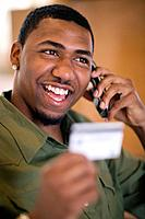 Man using credit card and cell phone