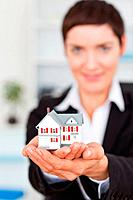 Portrait of a businesswoman holding a miniature house with the camera focus om the object