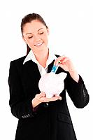 Beautiful woman in suit inserting a money bill in a pink piggy bank while standing against a white background