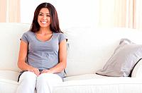 A smiling woman with brunette hair is sitting on a sofa in the livingroom