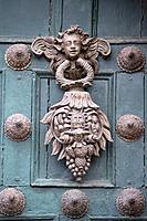 ornate door knocker on a green door of templo de la compania de jesus, cusco peru
