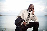 businessman using a cell phone at the water´s edge, south caicos turks and caicos islands