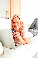 Portrait of a cute woman purchasing online in her living room