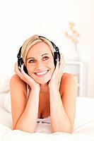 Portrait of a woman wearing headphones in her bedroom