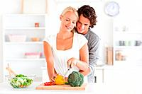 Couple slicing pepper in their kitchen