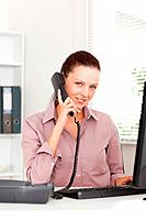 A businesswoman is telephoning at her workplace