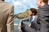 Businessmen talking on beach