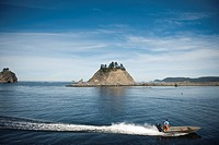 a man stands in a motorboat and drives through quileute river, la push washington united states of america