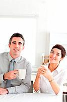 Smiling couple drinking coffee looking into the camera in a kitchen