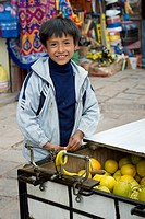 A Boy Smiles As He Tends A Cart Of Fruit At The Market, Cusco Peru