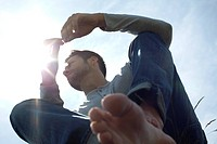 Man relaxing outdoors, backlit by sun, low angle view