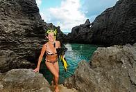 Woman coming out of ocean cove after snorkling, Bermuda Island, Atlantic