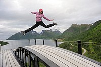 young woman jumping over the fjord Bergsfjorden Landscaping of the National Tourist Route The west coast of the island Senja has been selected as one ...