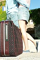 Italy, Tuscany, Young couple embracing with luggage in foreground