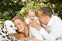 Germany, Bavaria, Father, mother and daughter with dalmatian in garden, smiling
