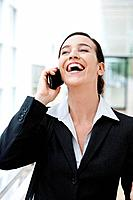Germany, Bavaria, Diessen am Ammersee, Young businesswoman talking on mobile phone, laughing